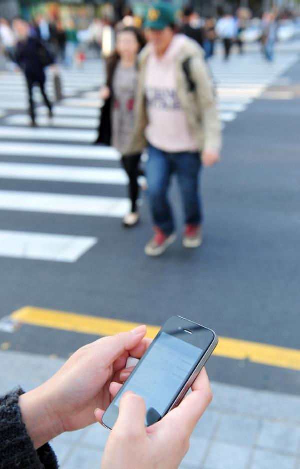 A woman uses her smartphone on a street in Seoul. New rules are on the way to protect consumers from expensive data roaming fees, but for now, phone owners can take steps to help themselves.