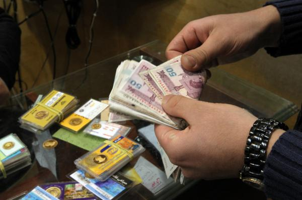 An Iranian man counts banknotes after exchanging a gold coin for cash in Tehran on Monday. Gold coins were being exchanged for over 10 million rials as the Iranian currency continues to lose value against the U.S. dollar.