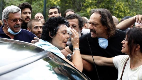 Communist party lawmaker Liana Kanelli enters her car after protesters threw yogurt on her face as she tried to reach the Greek parliament during a 48-hour general strike in Athens in 2011.