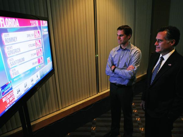 Mitt Romney watches primary election results with his son Josh in Tampa on Tuesday night. He won in Florida by the same margin he lost by in South Carolina.