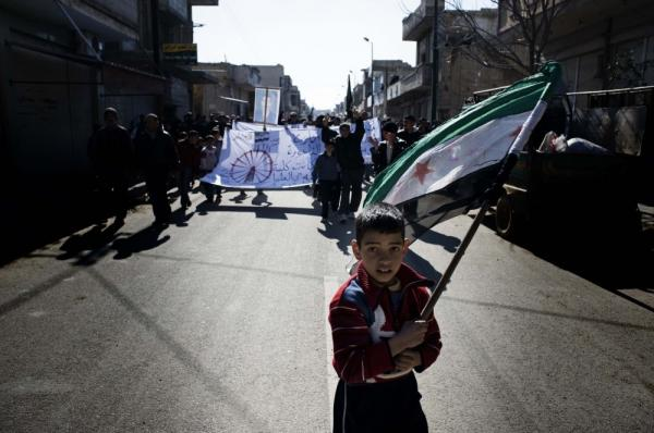 A young boy carries the Syrian-rebel adopted flag during an anti-regime demonstration in the Syrian village of al-Qsair, not far from Homs.