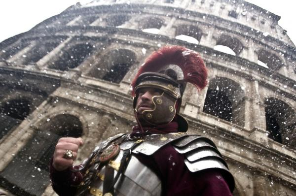 A man dressed as a Roman Gladiator stands in front of the ancient Colosseum as snowflakes fall in downtown Rome on Friday.