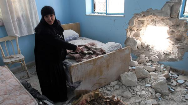 "In this photo taken during a government-organized media tour, Sister Verona, head of the Sednaya Covent, shows a room damaged by artillery fire Sunday in Sednaya, north of Damascus, Syria, Jan. 31, 2012. The Syrian government blamed the convent attack on ""armed terrorists."" Over the weekend, clashes broke out in several suburbs of the Syrian capital — with deadly results."