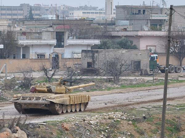 A Syrian army tank moving along a road during clashes with the Syrian army defectors, in the Rastan area in Homs province, central Syria, on Jan. 30, 2012.