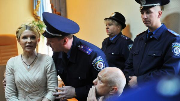 A police officer speaks to Ukraine's former prime minster, Yulia Tymoshenko, after she was convicted of abuse of power charges in a court in Kiev on Oct. 11, 2011. She is now serving a seven-year term, but her supporters say the charges against her were politically motivated.