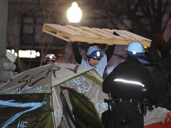 A U.S. Park Police officer removes a wooden structure from an Occupy D.C. protester's tent at McPherson Square in Washington, D.C., on Saturday.