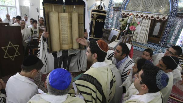 Iranian Jews look at the Torah scroll during a morning service for Shabbat, on the Jewish festival of Passover, at the Pol-e-Choubi Synagogue, in Tehran, Iran, April 23, 2011. Iran has the largest Jewish population in the Middle East outside Israel. Growing conflict between the two countries is affecting Iranian Jews in both places.