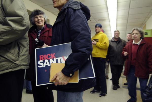 A caucus participant holds a Rick Santorum sign as people wait to get name tags during the Minnesota caucuses at Roseville Area Middle School on Tuesday in Little Canada, Minn.