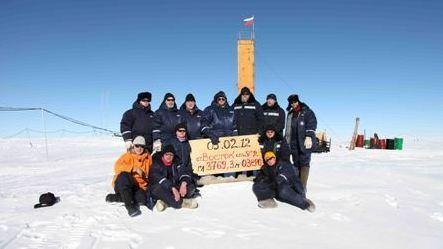 In Antarctica, Russian scientists posed at the site where they say they've drilled through to Lake Vostok. The sign indicates that the breakthrough happened on Feb. 5, 2012.