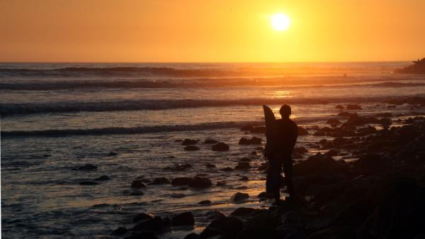 A surfer watches the waves just before sunset at Will Rogers State Beach in the Pacific Palisades area of Los Angeles.