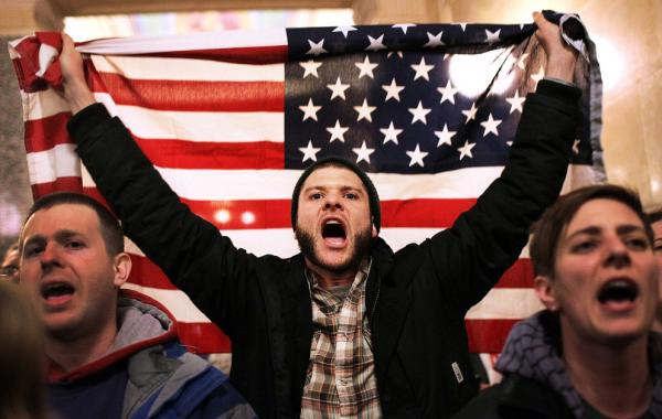 For so many reasons, Americans are seething. Here, a protestor shouts as he holds an American flag after storming the Wisconsin State Capitol on in Madison, Wis., March 9, 2011 after Republicans in the state Senate voted to curb collective bargaining rights for public union workers.