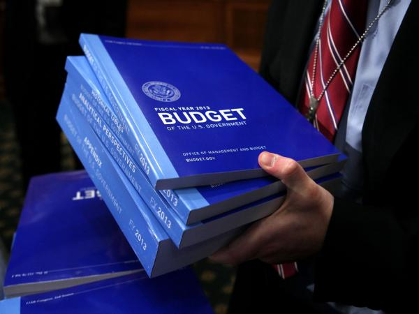 A congressional staffer collects copies of the president's 2013 budget request from the Senate Budget Committee on Monday in Washington, D.C.