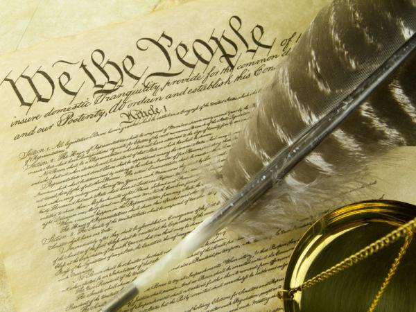 US Constitution replica arrangement with turkey feather quill pen and a golden scale below.
