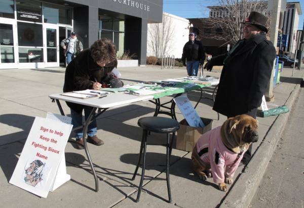 Charles Tuttle, a backer of the University of North Dakota's Fighting Sioux nickname, watches as a woman signs petitions supporting the nickname on Tuesday, Feb. 7.