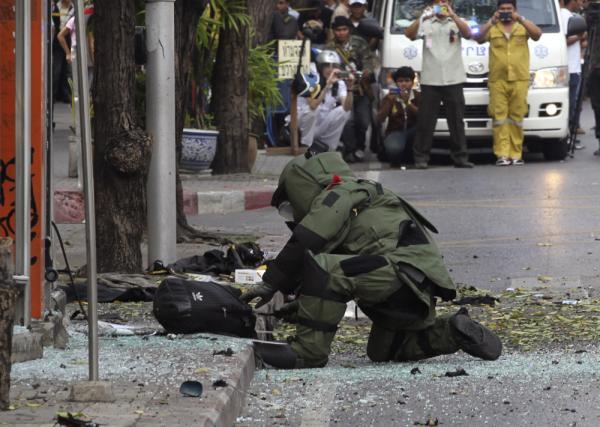 A Thai Explosive Ordnance Disposal (EOD) official examines a backpack that was left on the bomb site by a suspect bomber in Bangkok on Tuesday.