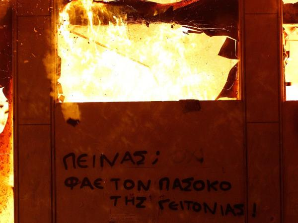 "A message on a burning building in the center of Athens saying ""Hungry? Eat your local Pasok politician"" is seen during the demonstration against the new austerity measures in Syntagma Square on Feb. 12, 2012 in Athens, Greece. Greece's creditors have demanded further austerity measures before approving a new bailout from the European Union."