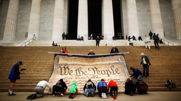 "Americans are always searching for a ""more perfect union."" Volunteers roll up a giant banner printed with the Preamble to the U.S. Constitution during a demonstration against the Supreme Court's Citizens United ruling at the Lincoln Memorial in Washington on Oct. 20, 2010."