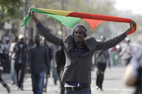 An anti-government protester carries a Senegalese flag as he walks near a central square that protesters had planned to occupy before being rebuffed by police, in central Dakar, Senegal on Thursday.