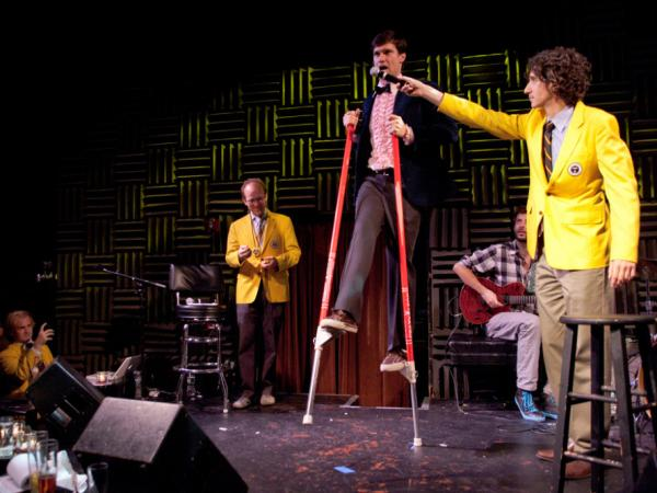 "Dan Rollman, the co-founder of RecordSetter, holds up a microphone to Rob Lathan, who currently holds the world record for <a href=""http://recordsetter.com/world-record/leg-kicks-stilts-while-singing-new-york-new-york/4703"">completing 81 leg kicks</a> on stilts while singing ""New York, New York,"" at a World Record Appreciation Society event in New York City."