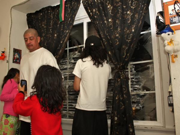 Pedro Jimenez and three of his kids, in the living room of their East Oakland, Calif., apartment. JPMorgan Chase hasn't hired a management company to fix the shattered window panes or make other repairs.