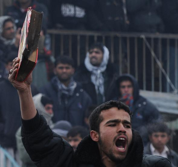An Afghan demonstrator holds a copy of a half-burnt Quran, allegedly set on fire by soldiers at Bagram Air Field, during a protest outside the base today.