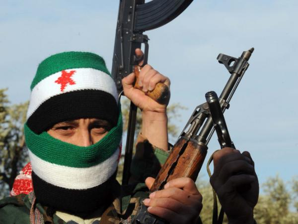 A member of the Free Syrian Army with his face covered with the pre-Baath Syrian flag patrols with comrades in Idlib in northwestern Syria on Feb. 18, 2012. Some commentators have proposed supplying the rebels with munitions.