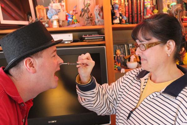 Suzanne Gangi removes a six-inch nail from her husband Tony's nose.