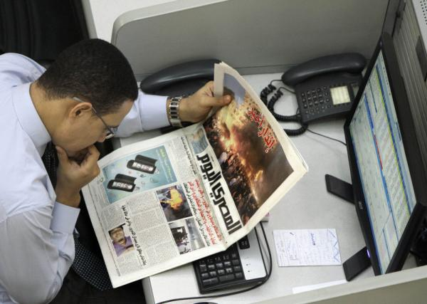 An Egyptian stock trader reads a copy of the <em>Al-Masry Al-Youm</em> newspaper last November. Critics say the newspaper is reluctant to criticize the ruling military council and has engaged in self-censorship.