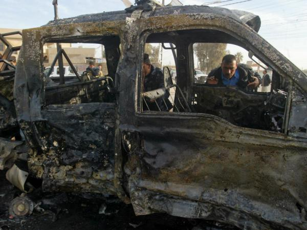 An Iraqi policeman inspects a destroyed vehicle at the site of a blast in the northern city of Kirkuk earlier today (Feb. 23, 2012).