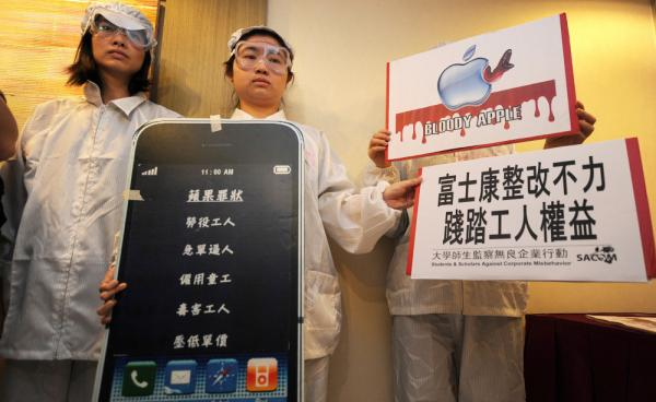 A group of protesters demonstrate outside Foxconn's annual meeting in Hong Kong last year. Working conditions at the company's plants have brought criticism on Apple.