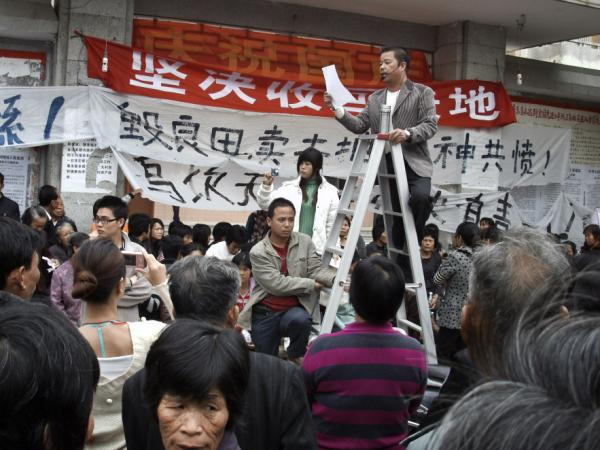 Xue Jinbo, a key representative from Wukan village, speaks to the villagers from a stepladder during a protest in Wukan in December. Xue Jinbo, detained during a protest, died in police custody.