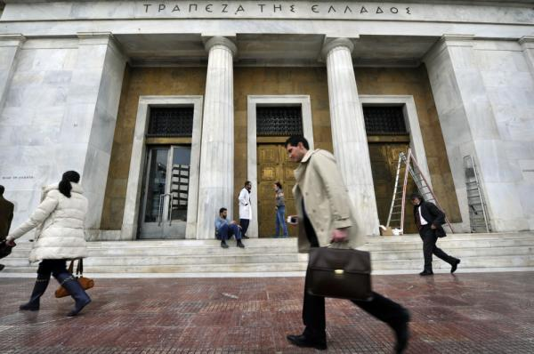 People walk past the Bank of Greece headquarters in Athens. Greece toughened its stance to push creditors to accept a debt swap and take heavy losses, just one day before the Thursday deadline for completion of the deal to avert default.