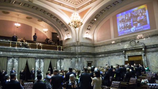Legislators and staff celebrate on the Senate floor after adjournment. By Austin Jenkins.