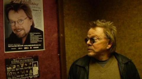 Paul Williams stares at a poster advertising an upcoming performance in the documentary <em>Paul Williams Still Alive</em>.