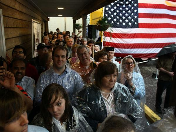 Supporters take cover from the rain as they listen to Republican presidential candidate Mitt Romney speak at the Whistle Stop cafe March 12, 2012 in Mobile, Alabama. Alabama and Mississippi hold their primaries today.