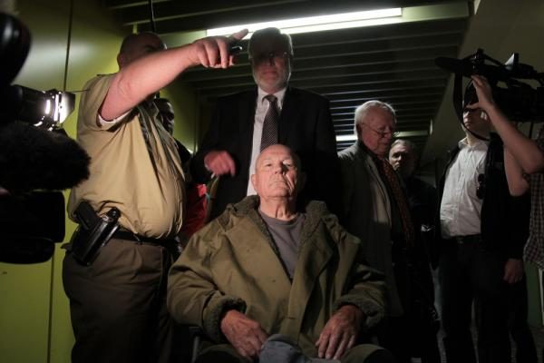 John Demjanjuk emerges from the courtroom with his lawyers after a judge sentenced him to five years in prison for charges related to 28,060 counts of accessory to murder in May 2011 in Munich, Germany.