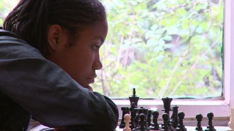 Rochelle, one of the kids in <em>Brooklyn Castle</em>, examines a chess board.