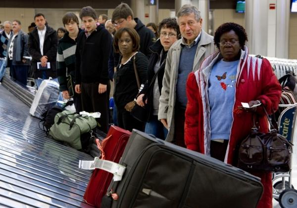 International airline travelers wait for their luggage at Dulles International Airport near Washington, D.C.