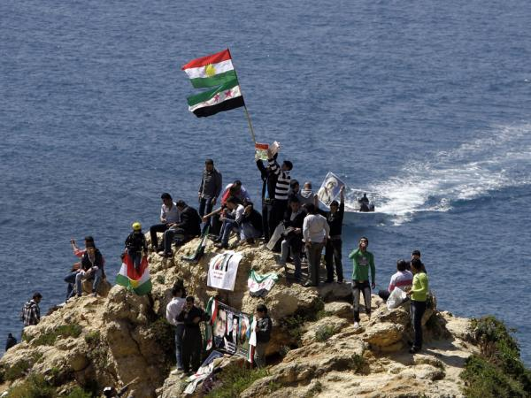 Kurds hold up Syria's pre-Baath and Kurdish flags, chanting slogans against the Syrian regime as they celebrate Noruz spring festival in the lebanese capital Beirut on March 21, 2012.