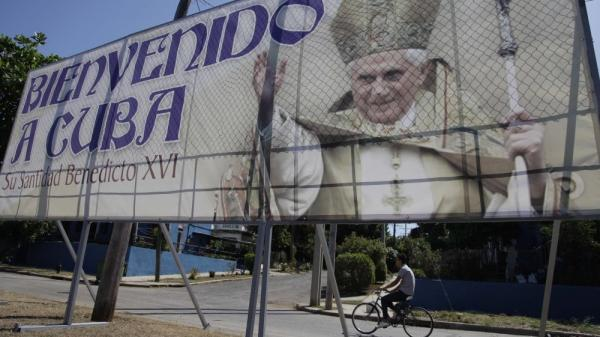 A man rides his bicycle past a billboard welcoming Pope Benedict XVI, just days before his arrival, in Havana, Cuba. Pope Benedict's trip to Latin America includes Mexico and Cuba.