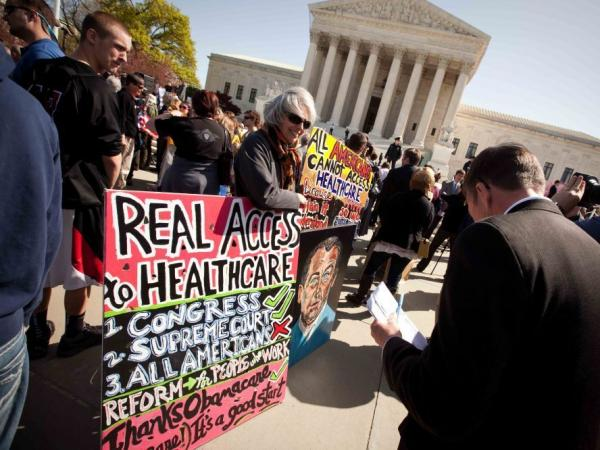 Amid a crowd of Tea Party activists, a supporter of President Obama's health care overhaul displays a sign outside the Supreme Court on Monday.