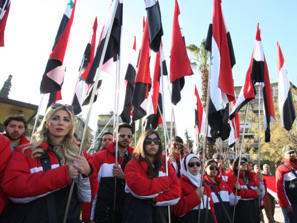 Syrians hold up the national flag as they line the street as the coffins of some 27 people who were killed in two bomb blasts the previous day leave the Othman mosque following their funeral service in Damascus on March 18, 2012.