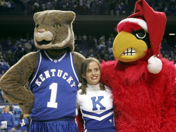 "A cheerleader for the Kentucky Wildcats stands between the mascots for Kentucky and the Louisville Cardinals as they sing ""My old Kentucky Home"" after the game at Rupp Arena on December 17, 2005 in Lexington, Kentucky. In our second hour, die hard fans talk about long standing team rivalries in their town."