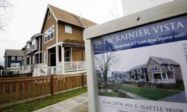<p>A home in Seattle is advertised for sale in January. A housing boom 140 miles north in Vancouver, British Columbia, is being fueled by buyers from India and China, while building remains at a standstill in Seattle, one housing expert says.</p>