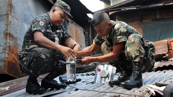 Filipino soldiers install solar light bulbs through a roof in a shantytown in Manila, Philippines. The bulbs are actually old plastic soda bottles filled with water and bleach, and powered by the sun.