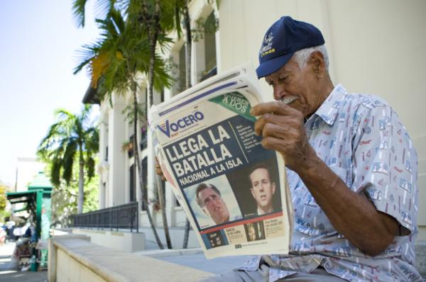 "Carlos Diaz, 84, reads local newspaper ""El Vocero"" with a front page depicting both Mitt Romney and Rick Santorum and a headline reading, ""The National Battle Arrives on the Island."""