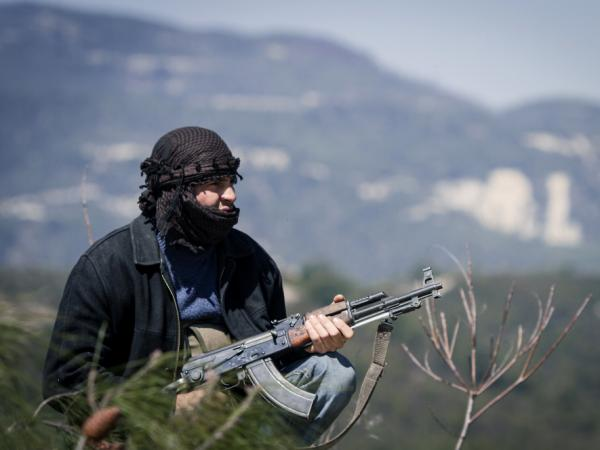 A member of the Free Syrian Army takes position as heavy fighting erupts on a nearby hillside during an attack by his unit in the mountains, west of Idlib, on March 19, 2012.