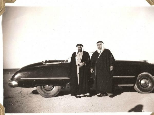 Yousef Ahmad al-Ghanim, a prominent Kuwaiti businessman who went on to found many businesses, and Tom Mohney, a Bechtel employee standing to his right, pose in front of an Oldsmobile in the Arabian Gulf in 1950.