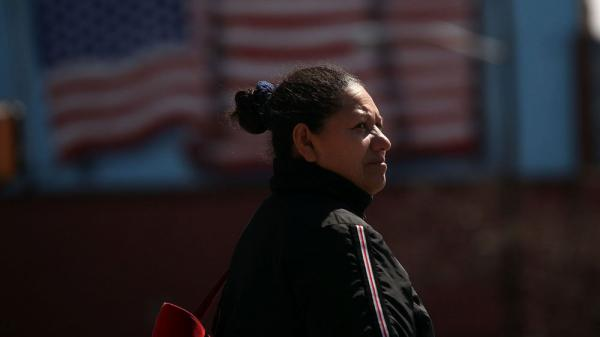 A Hispanic woman walks down a street in Union City, N.J. In a new study, the Pew Hispanic Center asked Hispanic-Americans how they identify themselves.