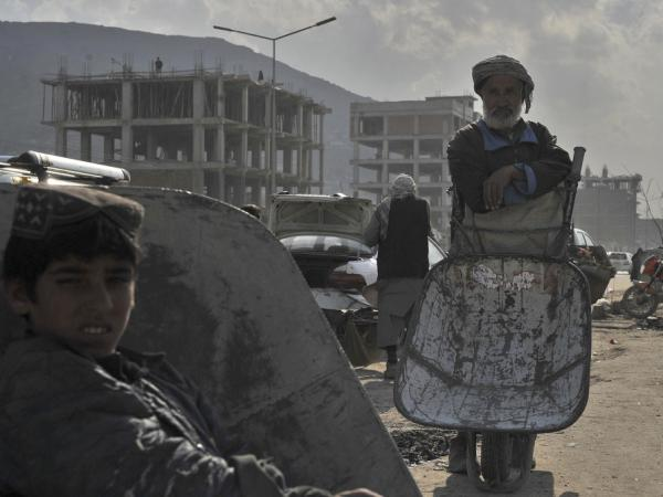 An elderly Afghan man stands with his wheelbarrow in Kabul on April 3, 2012. Afghans are increasingly concerned about security.